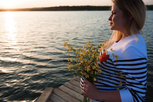 夕暮れ時の川で幸せと誇りに思って妊娠中の女性の肖像画。 Premium写真