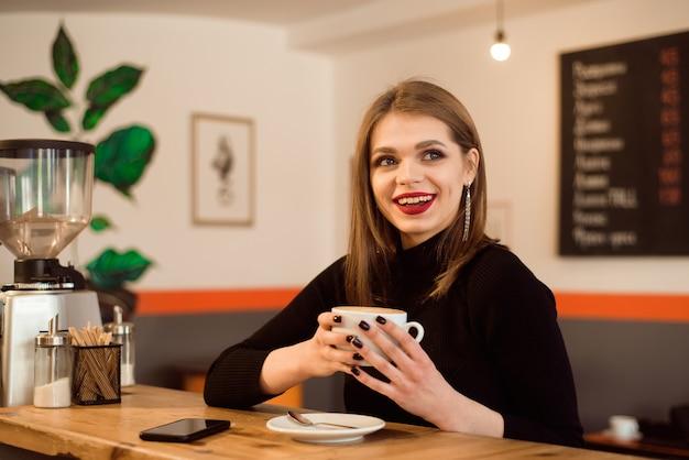 Портрет молодой женщины, пить кофе в кафе. Premium Фотографии