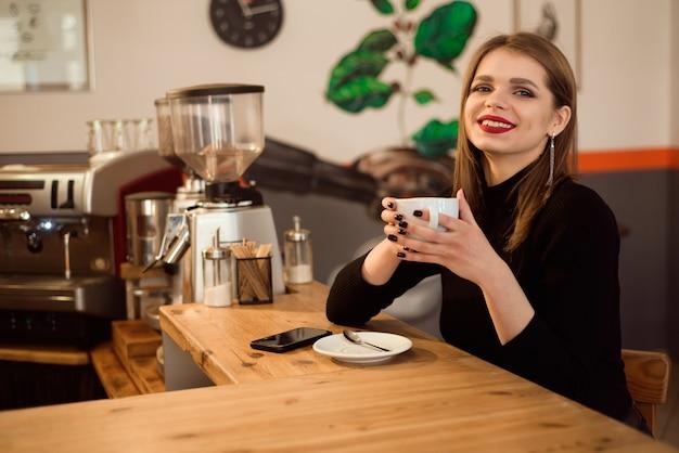 カフェでコーヒーを飲む若い女性の肖像画。 Premium写真
