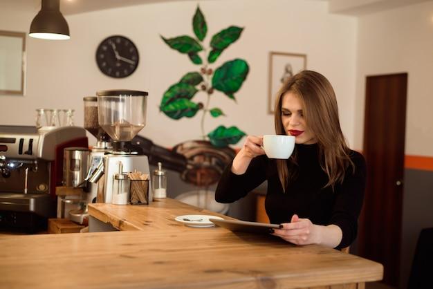 Молодая женщина с помощью планшетного компьютера в кафе. Premium Фотографии