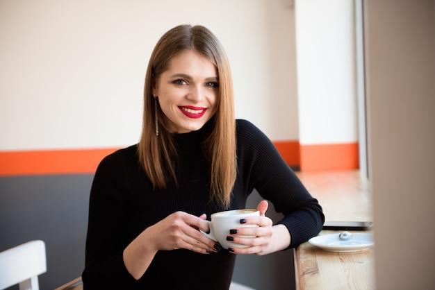 Жизнерадостная молодая женщина выпивая теплый кофе наслаждаясь им пока сидящ в кафе. Premium Фотографии