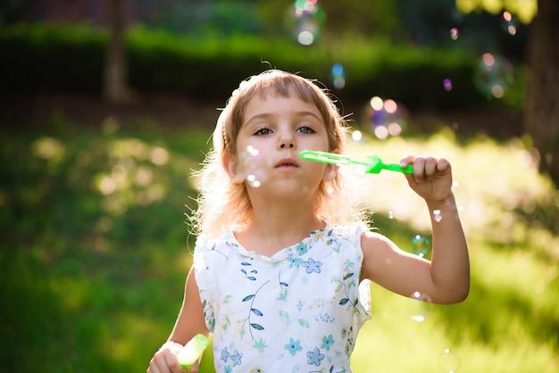 日当たりの良い夏の夜に泡を持つ少女 Premium写真