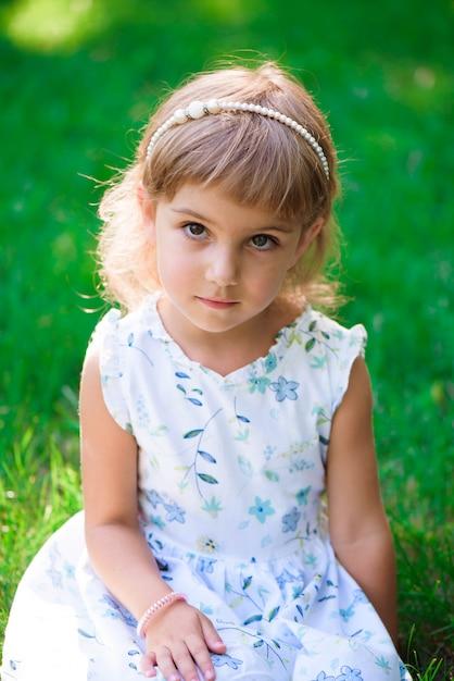 緑の芝生に座っている笑顔の少女の肖像画。 Premium写真