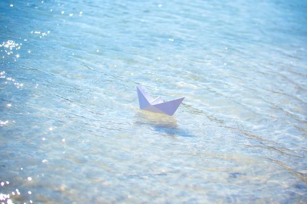 青い水の波の上の紙の船 Premium写真
