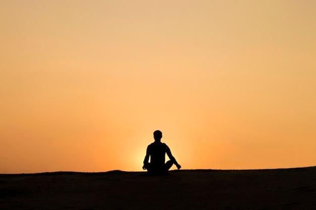 Человек на закате расслабляется, занимаясь йогой Premium Фотографии