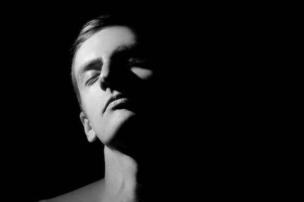 白黒写真、大きな顔の半分の顔が点灯 Premium写真