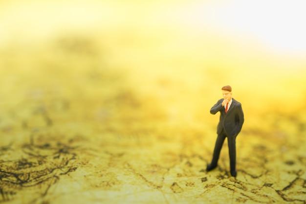 ビジネスマンのミニチュア人図立っていると世界地図を考えています。 Premium写真