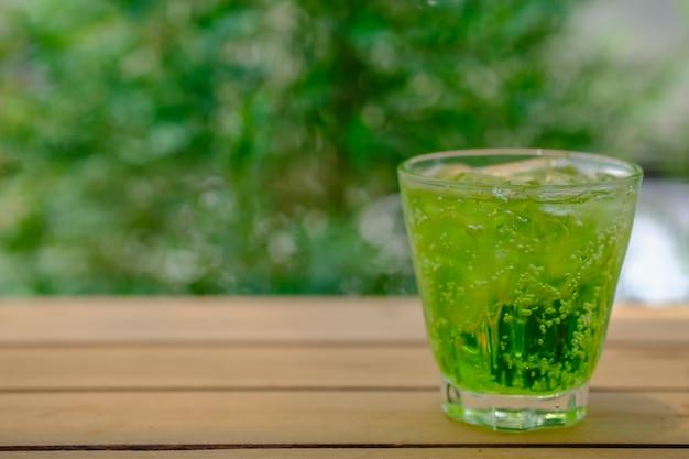 庭の自然と木製のテーブルの上のアイスグリーンソーダのガラス Premium写真