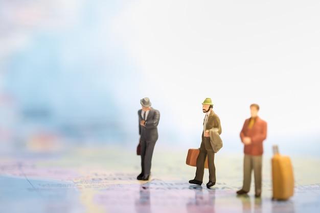 スーツケースと手荷物を歩くと立っているビジネスマンミニチュアフィギュアと世界地図で時計を見る。 Premium写真
