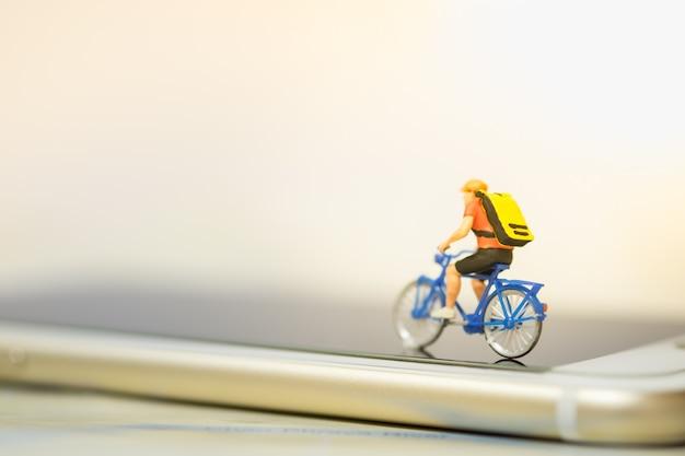 ミニチュアフィギュア男はスマートフォンでバックパックと自転車に乗る。 Premium写真