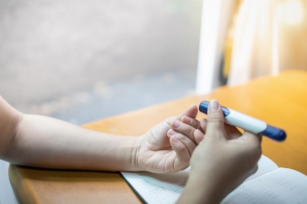糖尿病の血糖値を確認するために指にランセットを使用して女性の手のクローズアップ。 Premium写真