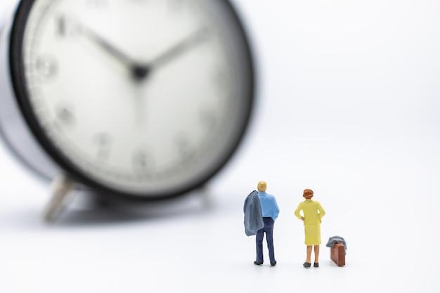 実業家と女性のミニチュア図立っていると白のヴィンテージの丸い時計を探しています。 Premium写真