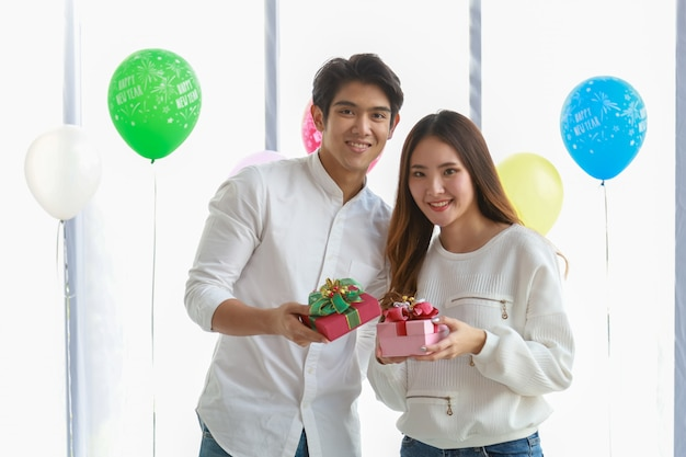 С новым годом и пара концепция. азиатская улыбка молодого человека и женщины и держать милую подарочную коробку в партии. Premium Фотографии