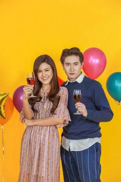 カップル、新年、バレンタイン、休日の調味料のコンセプト。ハンサムなアジア人と立っていると黄色の背景とカラフルなパーティーバルーンと赤ワインのガラスを保持している美しい女性の肖像画。 Premium写真