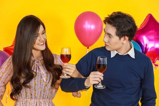 ハンサムなアジア人と目を見て、黄色の背景とカラフルなパーティーバルーンと赤ワインのガラスを保持している美しい女性の肖像画。 Premium写真