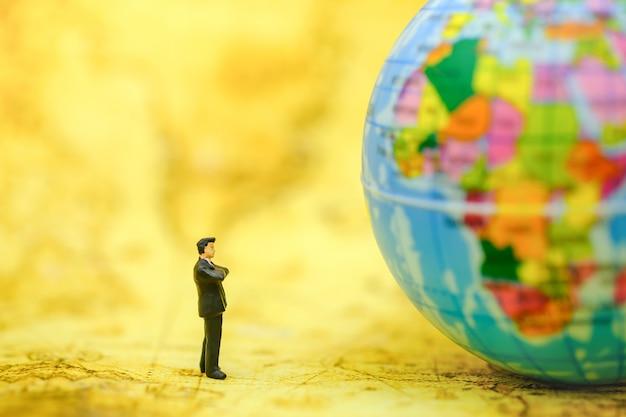 ビジネスマンのミニチュアの人々図地図上に立っていると地図上のミニ世界ボールを探しています。 Premium写真