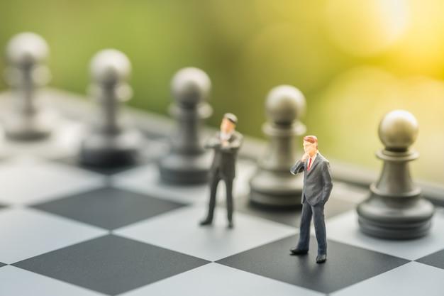 Два бизнесмена миниатюрные мини люди фигуры стоя на шахматной доске с шахматными фигурами. Premium Фотографии