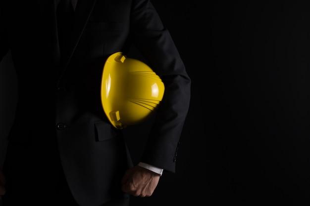 Инженер в черном костюме на черном фоне Premium Фотографии