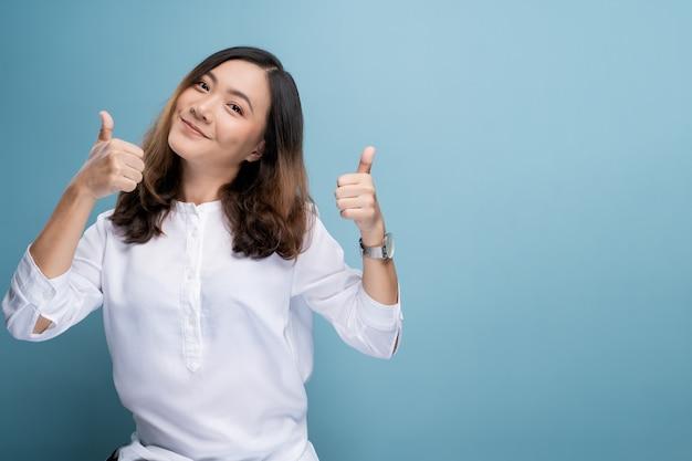 Счастливая женщина показывает большой палец вверх на фоне Premium Фотографии