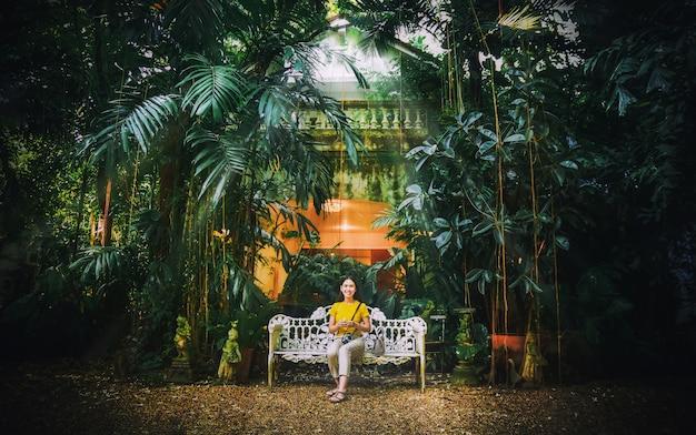 自然緑公園ビンテージトーンの白いベンチマークに座っているアジアの女性 Premium写真