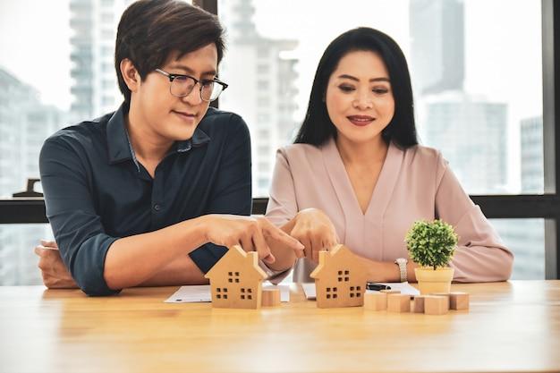 Пара выбор модели дома, чтобы купить дом Premium Фотографии