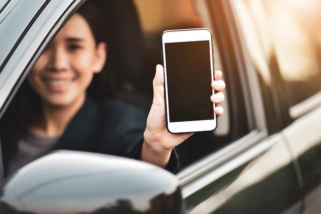 車に座っている携帯電話の画面を示す女性持株スマートフォン Premium写真