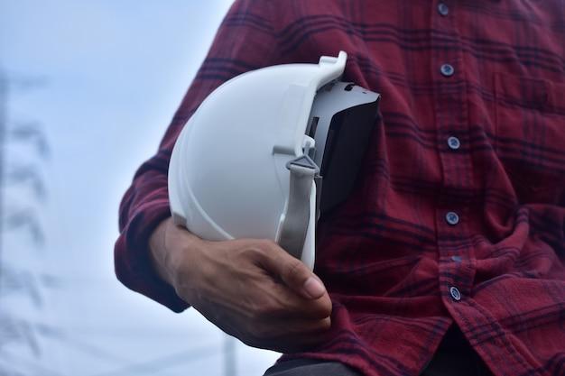 エンジニアは白いヘルメット安全ヘルメットを保持します Premium写真