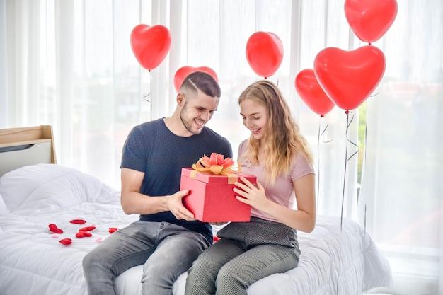愛のバレンタインの日の愛の寝室の幸福のギフトボックスを与えるカップル Premium写真