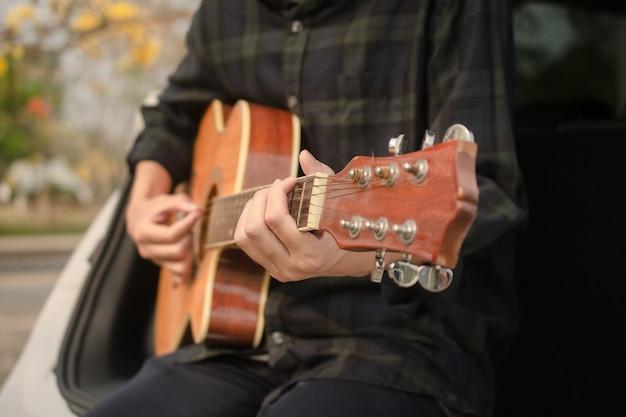 Человек играет на гитаре в машине Premium Фотографии