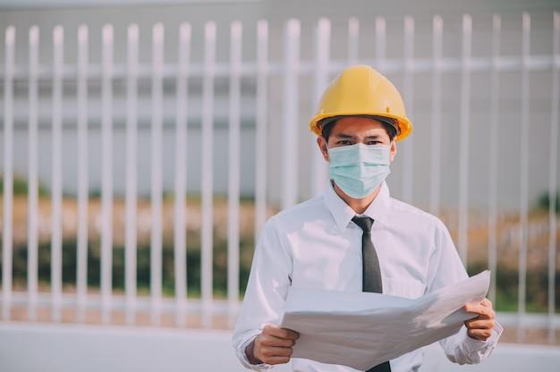 Инженер держит синий фон печати строительной площадки Premium Фотографии