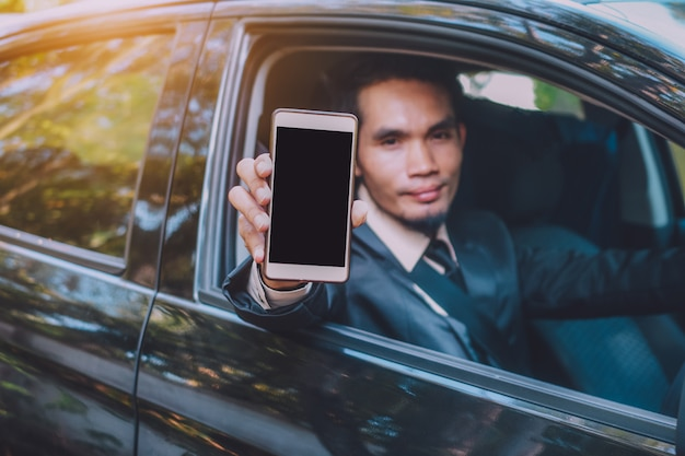 Бизнесмен, проведение смарт-телефон и сидя в автомобиле Premium Фотографии