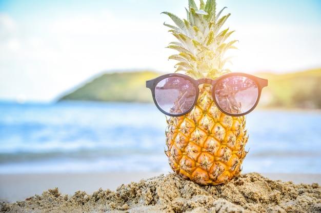 Солнцезащитный бокал на ананасе на фоне пляжа с видом на море, концепция летнего отдыха Premium Фотографии