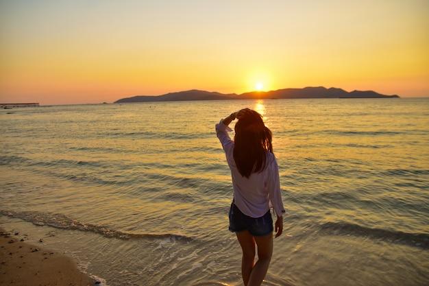 夜の黄金の時間に海の夕日を背景にビーチに立っている女性。 Premium写真