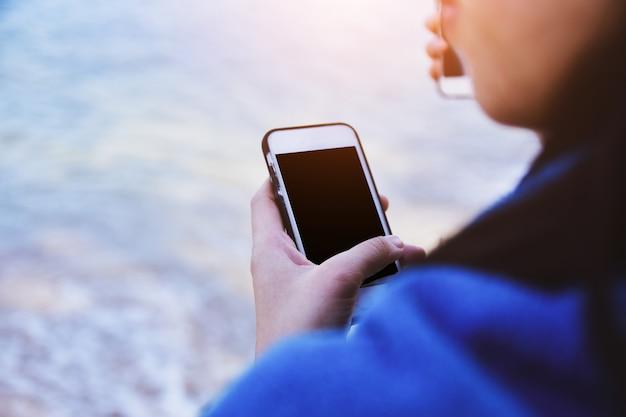 Женщины держат мобильный смартфон с использованием интернет-технологий в море Premium Фотографии