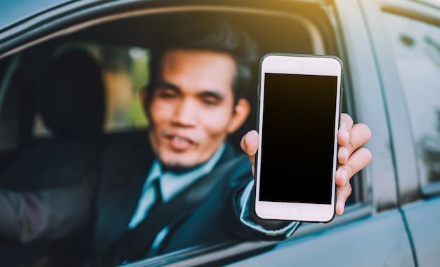 Мужчина держит мобильный смартфон, показывая на экране телефона и сидя автомобиль Premium Фотографии