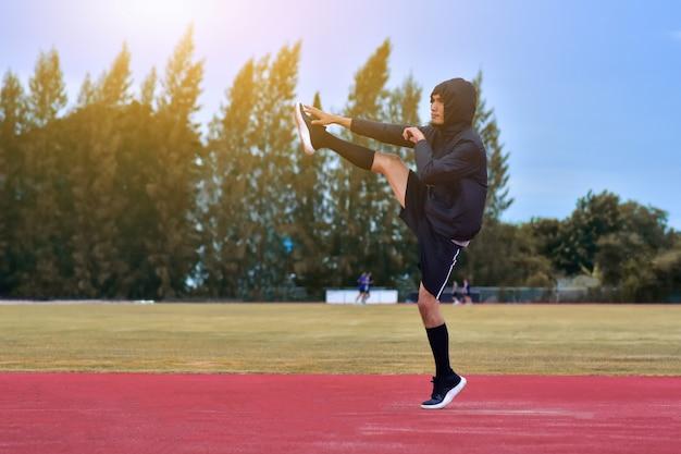 ランナーの男は、実行またはジョギングの前に体をワームします。 Premium写真