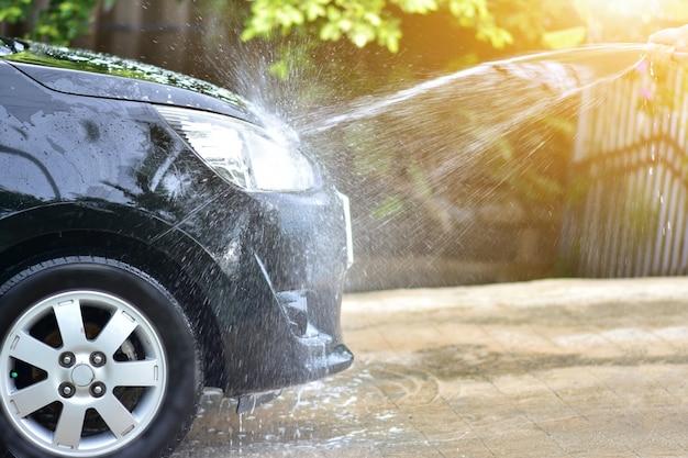自宅の日光で車を掃除する人 Premium写真