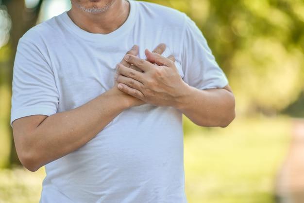 年配の男性の心臓病は、運動中に彼の心に彼の手を保持しています。心臓の健康問題 Premium写真