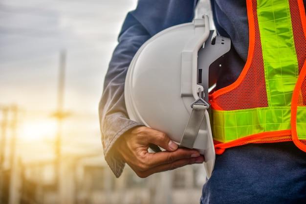 ヘルメットを保持しているエンジニア建設労働者プロの安全作業産業建築者マネージャーサービス Premium写真