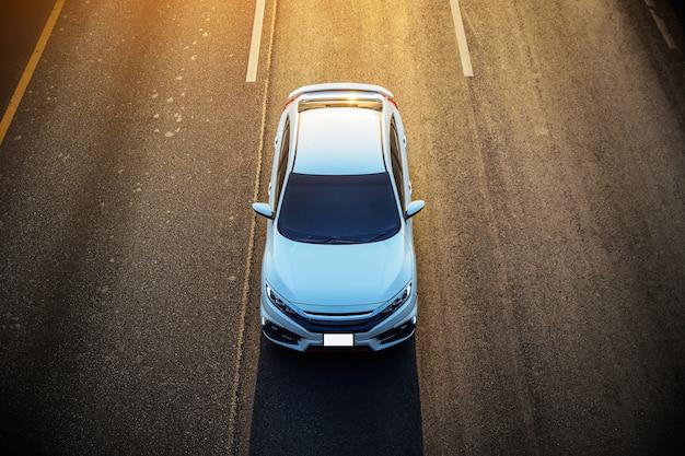 Вождение автомобиля по дороге вечером для поездки домой Premium Фотографии