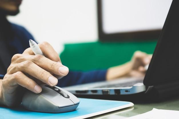 ペンを押しながら仕事でコンピューターノートパソコンのマウスコントロールを使用しての実業家 Premium写真