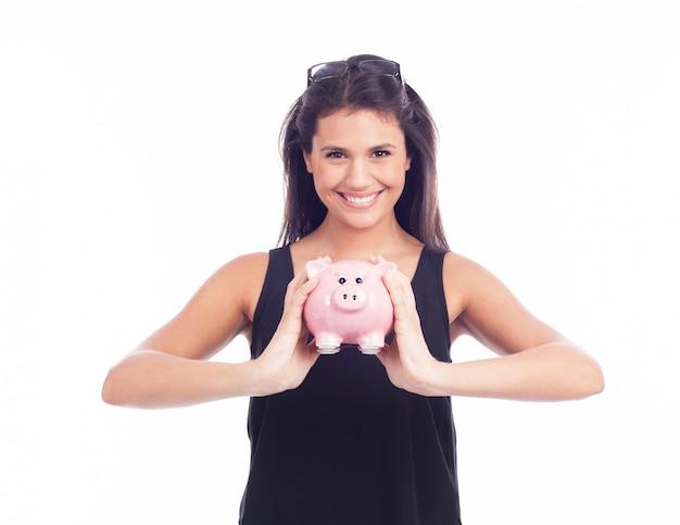 Молодая женщина в очках счастлива с копилкой Premium Фотографии
