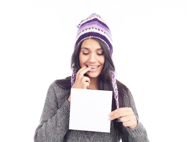 Портрет молодой женщины с свитер и перуанской шляпе шерстяной холдинг знак карты. белый фон . изолированный Premium Фотографии