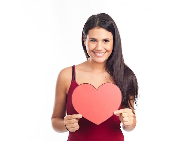 美しい幸せなブルネットの女性を保持していると大きな赤いハートを表示 Premium写真