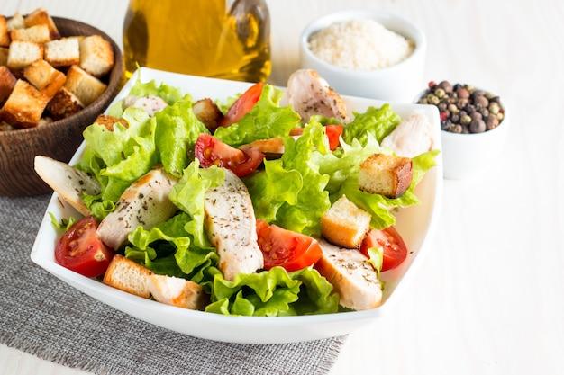 木製のテーブルの上の白いボウルにシーザーサラダ Premium写真