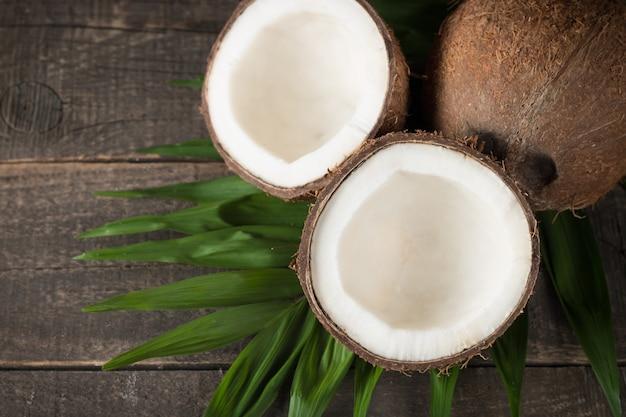 Кокос с зелеными листьями на фоне деревянные. Premium Фотографии