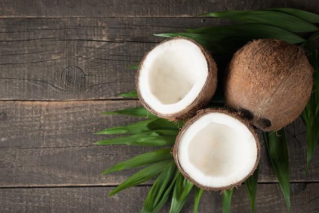 木製の背景に緑の葉とココナッツ。 Premium写真