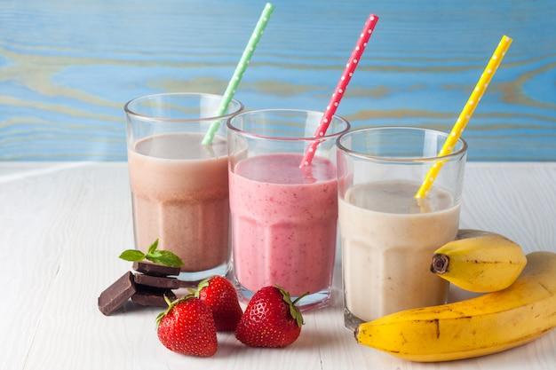 Стаканы молочных коктейлей из разных фруктов Premium Фотографии