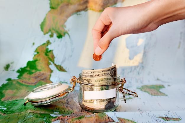 旅行のためのお金を集めるマップ上の現金の節約(紙幣と硬貨)の貯金箱としてガラス錫 Premium写真