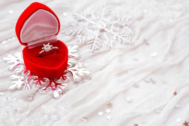 Обручальное кольцо с бриллиантом в красной подарочной коробке на белом Premium Фотографии